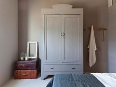 grey wardrobe painted out to match walls, vintage suitcases on display in corner