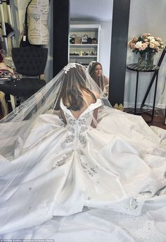 Candid moment: The bride sat in her incredible gown in front of the mirror before walking down the aisle to her husband Gary Clark Jnr