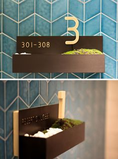 This modern hotel in Hong Kong includes room signage that features pebbles and moss in a small wall-mounted planter. #HotelDesign #InteriorDesign