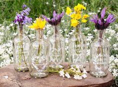 Botellas de cristal con flores primaverales