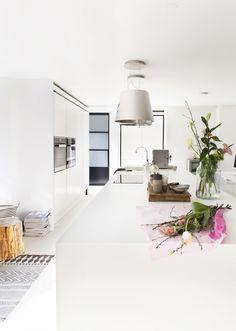 Witte keuken met kookeiland en mooie afzuigkap met de looks van een lamp