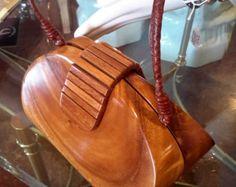 Suavemente utiliza auténtico Timmy Woods Acacia madera bolsa Mide 5.5 pulgadas de alto y 9 pulgadas de largo, la cadena es de 23 pulgadas Buena condición... hay una pequeña zona que tiene un chip de superficie y un par de pequeños golpes en la madera en algunos puntos