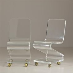 A Pair of Lucite Z-Shaped Chairs on Brass Wheels
