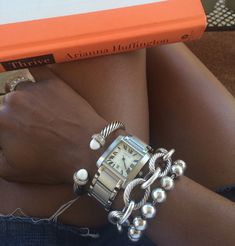 Stacked Bracelets with Arianna Huffington's Thrive on the side :-) Tiffany, Cartier, David Yurman