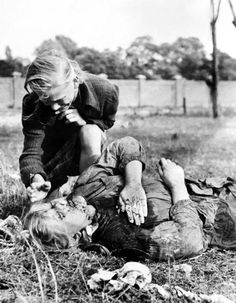 12 years old girl, Kazimiera, crying at dead body of her 14 years old sister, Andzia, shot by the Nazis - Warsaw, September 1939, photo by Julien Bryan