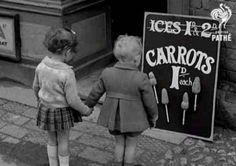 "During World War II, when sugar was rationed to 8 ounces per adult per week, some vegetable alternatives were introduced. These girls don't seem too happy about the ""carrot-on-a-stick"" option. Image courtesy of the World Carrot Museum."