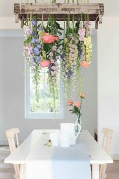 Deze bloemen zijn ondersteboven in een veilingkistje aan het plafond gehangen. Zo maak je een unieke sfeer in de eethoek!