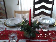 Centrotavola natalizio: piccolo cilindro in plastica con copertura in vera corteccia, erbe invernali e candela rossa al centro collocato sopra a una striscia rossa di cotone fatto all'uncinetto