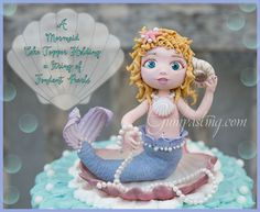 {A Mermaid Cake Topper Holding a String of Fondant Pearls}