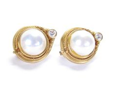 A pair of 18K yellow gold Omega-back earrings, each featuring a round cabochon mabe pearl, 12.5x8.8mm, each also accented with a bezel-set round white diamond in the top of the mounting, with rope trim around pearl, 12.6dwt #pearl #classic #wickliffauction