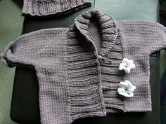 A warm unisex baby jacket with a wide ribbed lapel.