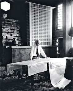 "FLW's photographer Pedro Guerrero: ""When I set up this shot of Wright in his studio at Taliesin, he hadn't shaved that morning and told me he wasn't about to. So I had to move the camera back to conceal the stubble, which actually improved the shot."" Behind Wright is a model of his 1912 design for the San Francisco Call building, a favorite of his that was never built."