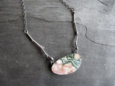 This necklace features a perfectly flat and gorgeous piece of ocean jasper. The pattern and colors are stunning - shades of pink and gray with with well defined orbs and lacy areas.  The stone is set in a fine and sterling silver setting. At each side I added a hand cast twig from a blueberry plant in my yard. The twigs are cast in solid sterling silver. A chain wraps around the neck and ends with a lobster clasp. I oxidized the silver and buffed it to bring out the detail.  Stone measures…