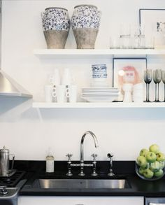 Open shelving above black countertops in a kitchen