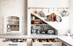 Exposed white brick kitchen with exposed pot rack and copper pots.