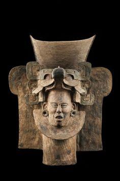 1/ OAXACA - Urna con tocado de ave de pico ancho. 83cm. Tombe 77. En relation avec glyphes sur masque ou en forme de casque entourant le visage. Bec large et incurvé. Deux encoches au-dessus des sourcils. Glyphe U représente entité surnaturelle évoquant oiseau mythique Cozaana, dieu du feu. Influence maya. Déformation du crâne.