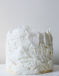 Hand-cut and detailed feathers were made from modeling chocolate, then gently positioned around a vanilla buttercream cake. Alana Jones-Mann