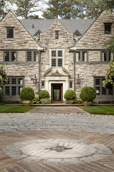 Front motor court with mill stone and family crest by Howard Design Studio.