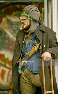 A Chechen fighter leans on a crutch near the Grozny presidential palace.
