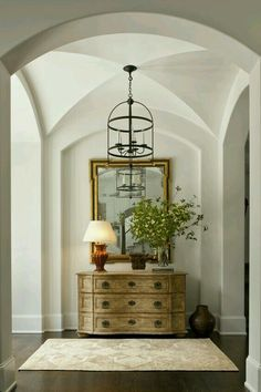 Lantern style chandelier.  Art. Large tabletop greenery. Lamp.  Entry table