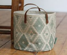 Baskets are an easy way to corral all sorts of items. The muted green pattern on this one works in almost any setting