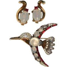 Trifari Moonstone Rhinestone Bird Pin Brooch Earring Set The hummingbird is marked TRIFARI and PAT. Pend. The earrings are marked TRIFARI with the crown.  The bird's body is a tear drop shaped moonstone. Each wing has graduated sized moonstones. The wings are bordered with red baguette stones. The tail has four moonstones and bordered with rhinestones. The head is encrusted with clear pave set rhinestones. The eye is a red cabochon.