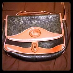 Vintage Dooney & Bourke Adorable black vintage bag The corners have some wear (as pictured), but don't stand out while being worn. The interior has some stains on the bottom, but again, can't be seen when items are in the bag. Interior pockets, and zipper. The back has a large pocket. Toggle closure, brown trim. Dooney & Bourke Bags