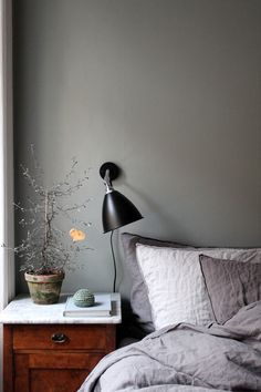 greyish green wall + black Gubi lamp.