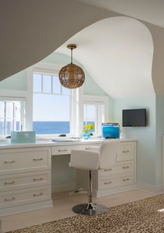 Lovely office set up in an eyebrow dormer with what look to be lovely views of the ocean. By George Penniman Architects.