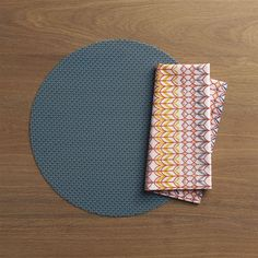 Durable polyester-vinyl placemat textures the table in an exclusive pattern that  takes its cue from fine knits.  Cotton napkins combine geometric and botanical elements in a complex design inspired by vintage iron grillwork. Placemat is 70% vinyl and 30% polyesterClean placemat with a damp cloth; air or towel dry and store flat100% cotton napkinMachine wash napkin cold, tumble dry; warm iron as neededMade in multiple countries.