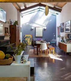 Sala integrada com uma mistura de móveis rústicos, peças de design e muita arte.