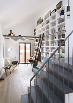 Floor to ceiling bookshelves with reading hammock! Best home library idea yet.