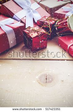 christmas concept. red gift and snow on wooden background. over light and vintage color tone