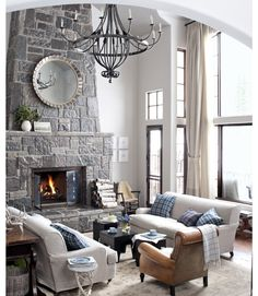 2 story stone fireplace with hearth, chandelier & windows