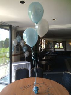 Three balloons attached to a weight, table decoration, with a beautiful arch behind awaiting the arrival of the Christening Cake.
