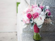 vwedding flowers were designed with pale pink and white peonies, two shades of pink ranunculus, pale pink astilbe, pink lisianthus, and grey dusty miller-both finished in a deep pink satin ribbon. A favorite!
