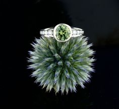 The unique green sapphire is securely bezel set, with a floating design that shows off the center stone from the side profile view. Each side of the center stone has seven diamonds descending in size on the tapered white gold band, and a smooth cathedral transition back up to the sapphire's bezel. This green Montana sapphire engagement ring is designed for and named after an Abby Sparks Jewelry client. #greenengagementring #uniqueweddingring #greengemstone #customring
