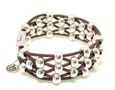 This beaded leather bracelet is created with 6 strands of high quality leather. The silver zamak metal beads are imported directly from manufacturers in Spain. The clasp is magnetic for easy on and off. You will love the quality and detail of the zamak metal in this bracelet. Zamak is a metal alloy that is deeply coated in silver and is world known for its weight, luster and durability. This bracelet is available in two sizes. Small fits wrists from 5 3/4 to 6 1/4. Large fits wrists...