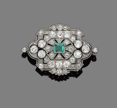 A belle époque emerald and diamond brooch, circa 1910. The openwork plaque, collet-set to the centre with a step-cut emerald, within a surround of millegrain-set graduated cushion-shaped, old brilliant and rose-cut diamonds