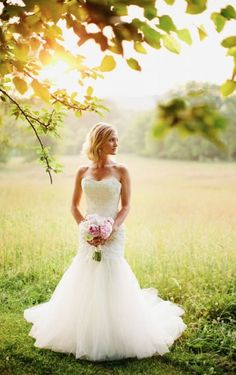 Tulle trumpet wedding dress with lace appliques and a strapless sweetheart neckline.