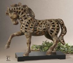 This horse sculpture features a heavily antiqued, textured ivory finish with matte black base.