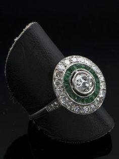 Anillo Art Decó ojo de pérdiz en oro blanco con orla de diamantes talla brillante, orla de esmeraldas y diamantes talla brillante en el centro. ANTEO SUBASTAS, 20004 SAN SEBASTIAN Estimation 1.400€