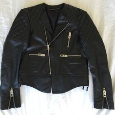 Balenciaga Quilted Leather Jacket - Sz 38 Iconic Balenciaga jacket in excellent/almost new conditions.  Black lamb leather biker jacket with quilted upper arms and shoulders and elbows by Balenciaga.  Collarless round neck.  Exposed slanted zip front.  Long sleeves with zip cuffs.  2 Zipped front pockets. 1 zipped chest pocket.  Press stud opening stays.  Lace-up sides.  Tiered hem detail.  Fully lined.  Cut for a close fit.  Hemline finishes at hip.  This was from the last season that…