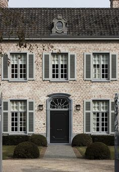 rounded boxwood, blue gray shutters, brick and stone