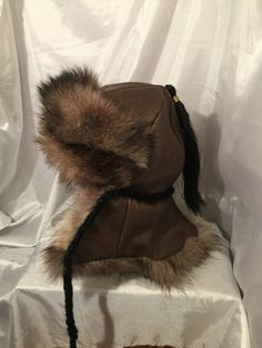 Mongolian, Russian, Norse Black timber wolf fur hat with ear flaps and fur down the back of the neck, brown leather top and black horse hair Recycled Leather, Leather Craft, Larp, Mens Fur, Ear Hats, Timber Wolf, Hats For Men, Cool Outfits, Character