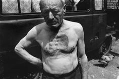 Thomas Dworzak - A member of the fire brigade in a National park. A fervent Stalinist, he had Stalin and Lenin tatooed on his chest as a conscript. Town of Zkhneti. GEORGIA. 1995 [***]