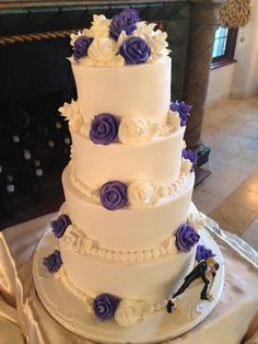 4 tier butter cream wedding cake with white  pearl beads around the bottom of each tier with purple and white flowers on top of each tier