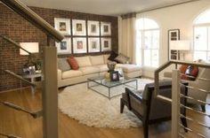 Die warme Farbe der freiliegenden Ziegelwand Komplimente der neutralen Ton der anderen Wand und Befestigungen in diesem Wohnzimmer. Foto von Carlyn und Firma Interieur + Design