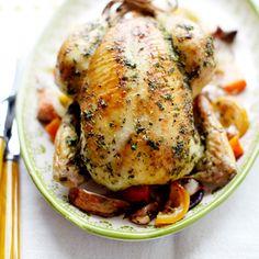 Verwarm de oven voor op 180 ºC. Meng 2 geperste knoflooktenen met de boter, het basilicum, zout en peper. Wrijf de kip ermee in. Kneus de rest van de knoflooktenen en doe een paar in de buikholte van de kip. Strooi de rest over de bodem van een...