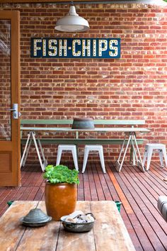 The home of Rebekah Cichero and family.  | Exterior of home and rear deck, featuring recycled bricks and timber.  Fish and chips sign and pendant lights, trestle table and bench – all One Small Room finds.  Railway trolley used as coffee table. Stools by Tolix from 1000 Chairs. Tin pots bought on a trip to Turkey.  Photo - Jacqui Way.